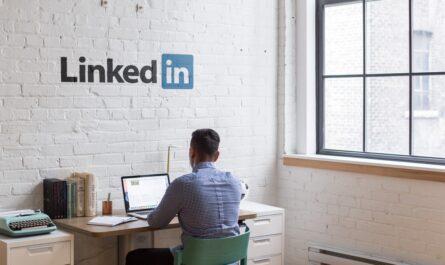 Mladík sedí pod logem sociální sítě LinkedIn.