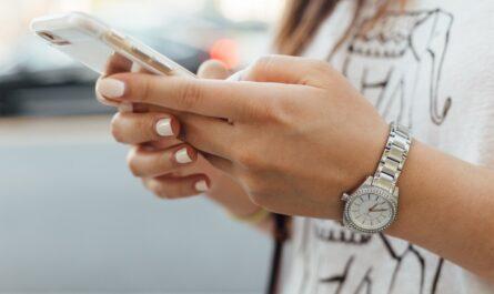 Mladá dívka využívá mobilní bankovnictví v telefonu.
